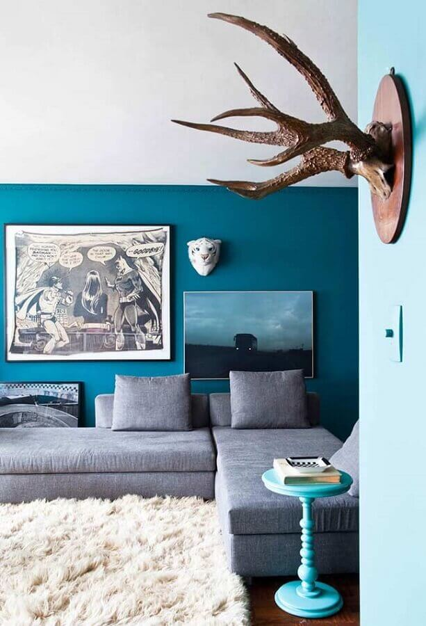 sala com parede azul decorada com tapete felpudo branco e sofá cinza Foto Casa Adore