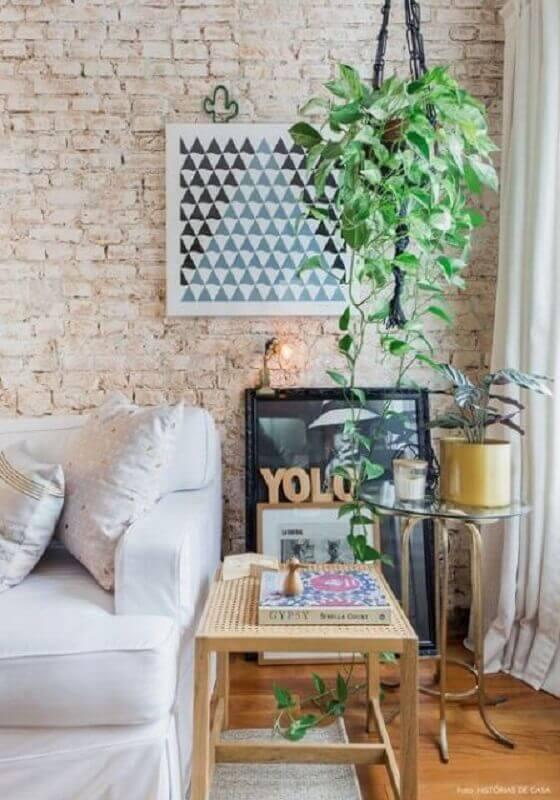 sala decorada com plantas pendentes e parede de tijolinho à vista Foto AchiZine