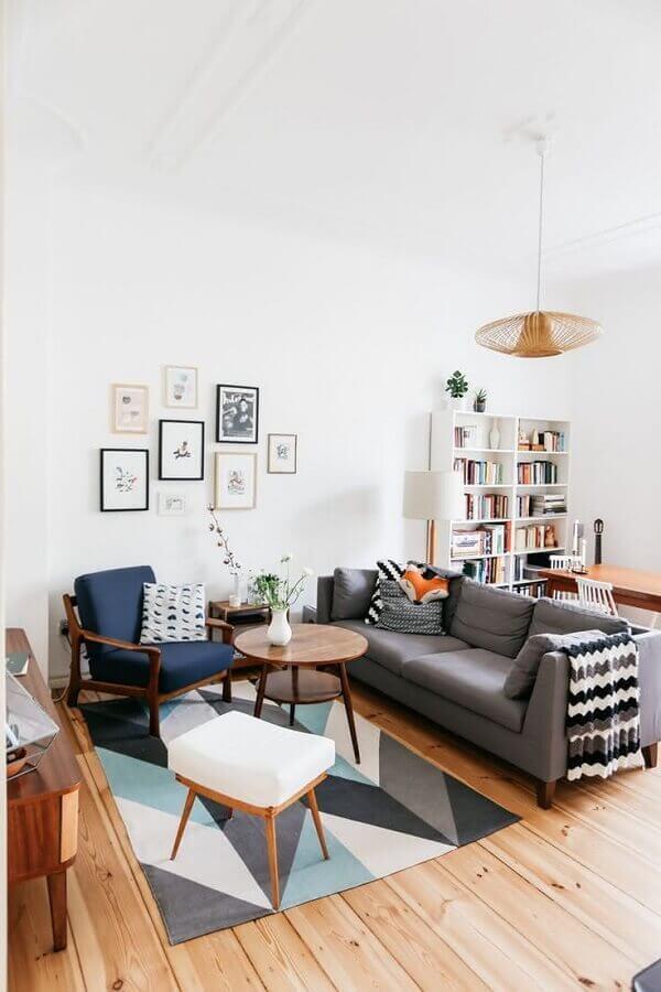 sala pequena decorada com poltrona de madeira e tapete geométrico Foto Behance