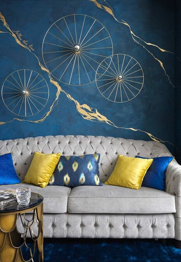 sofá cinza capitonê para decoração de sala azul Foto Archello