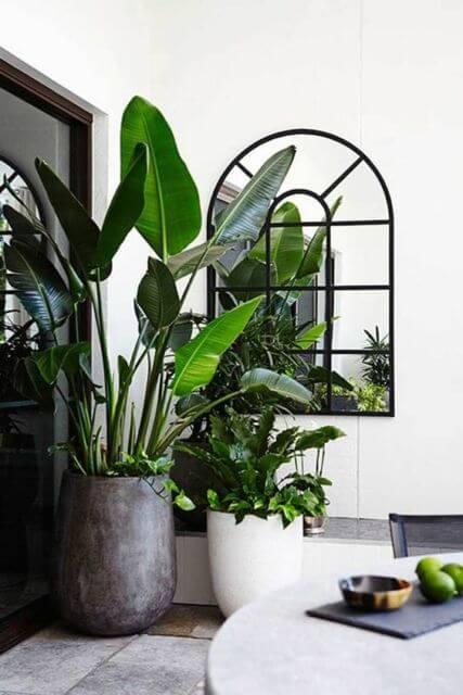 Sala de jantar com vasos grandes para plantas no canto, decorando o ambiente