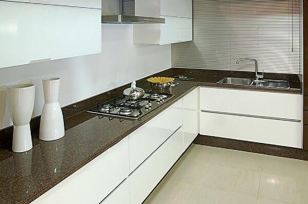 A bancada de cozinha granito café imperial se harmoniza com os armários brancos