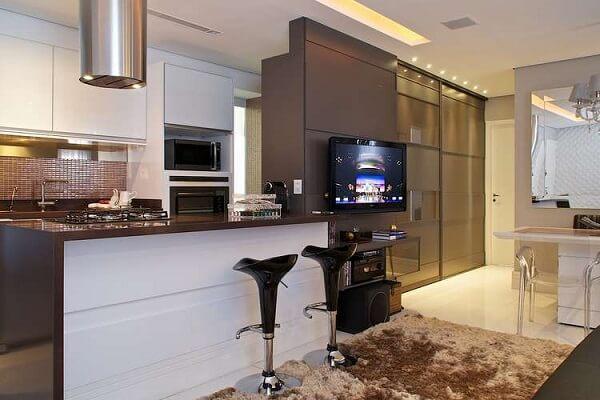 A bancada de cozinha granito café imperial serve de divisório de ambientes