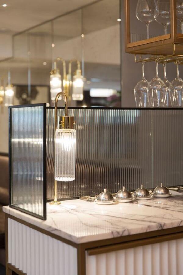 A estrutura com vidro canelado foi usada na bancada do restaurante