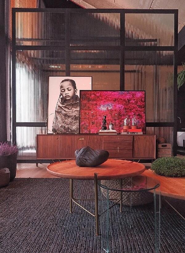 A estrutura feita de vidro canelado divide os ambientes dessa casa