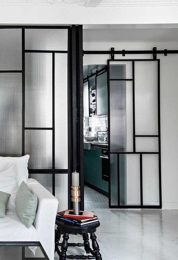 A porta de correr feita com vidro canelado separa os ambientes da casa