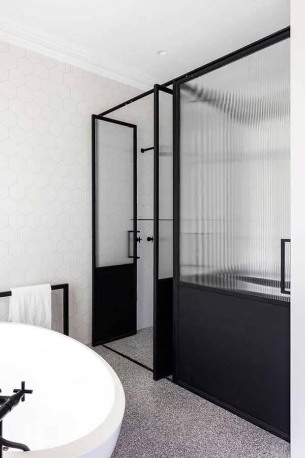 A porta de vidro canelado traz privacidade para aqueles que desfrutam da banheira