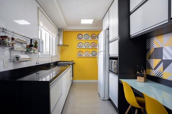 A cortina branca se conecta com o acabamento dos armários da cozinha