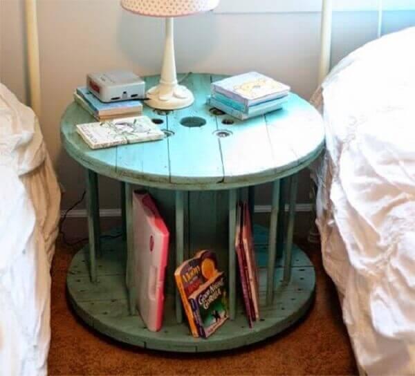 Criado mudo redondo antigo feito com carretel de madeira serve de apoio para livros