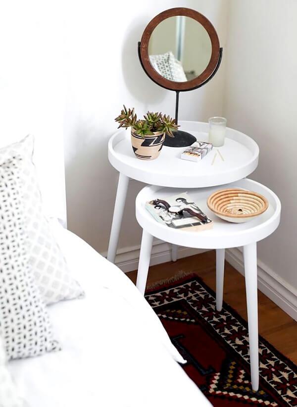 A mesa redonda criado mudo ocupa o pequeno espaço na lateral da cama