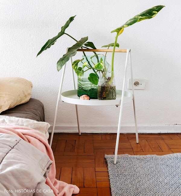 Criado mudo redondo branco serve de apoio para o vaso de planta