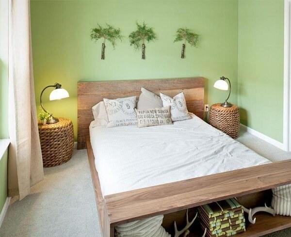 Criado mudo redondo posicionado ao lado da cama de casal é feito de cesto de vime