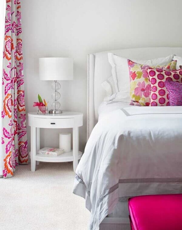O criado mudo na cor branca trouxe neutralidade para o quarto com cortinas e almofadas estampadas