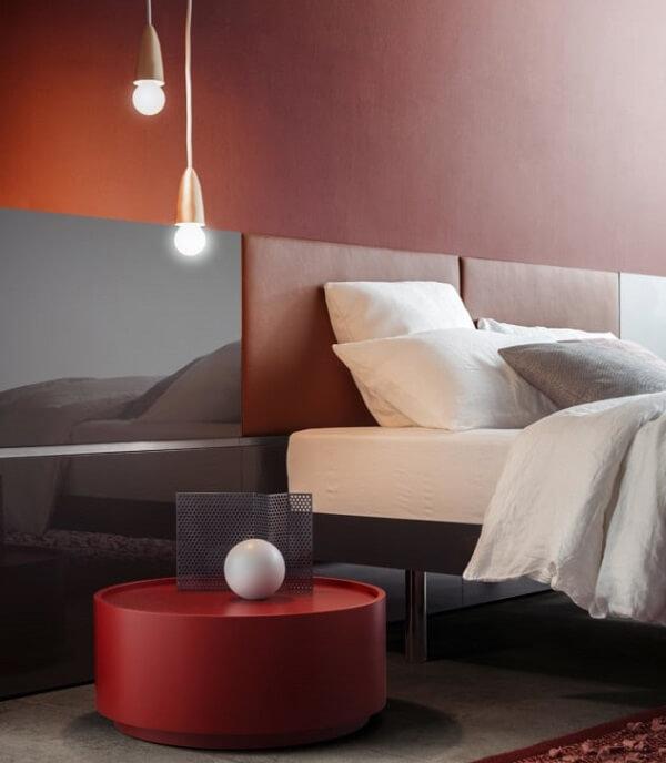 O criado mudo redondo vermelho se destaca na decoração do quarto