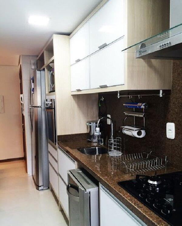 O granito café imperial realça a presença dos armários brancos da cozinha