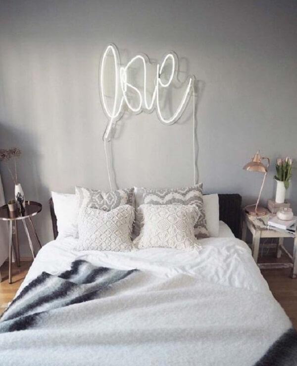 O letreiro luminoso neon com escrita LOVE decora o quarto do casal