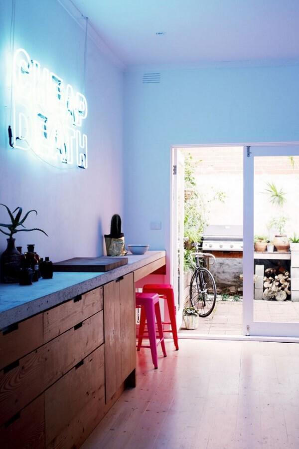 O letreiro luminoso neon em tom branco é discreto no ambient