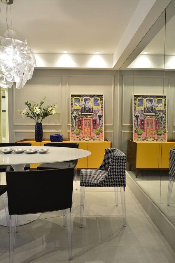Parede espelhada e aparador buffet amarelo decoram a sala de jantar