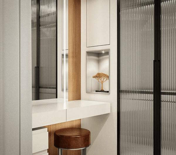 Penteadeira bancada branca e closet com porta de vidro canelado trazem charme para esse ambiente