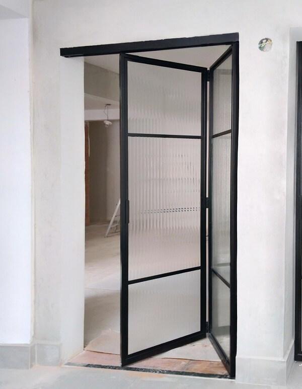 Porta articulada de ferro com vidro canelado
