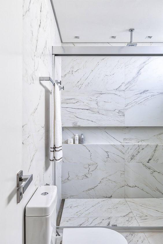 Banheiro com porcelanato marmorizado no box de chuveiro