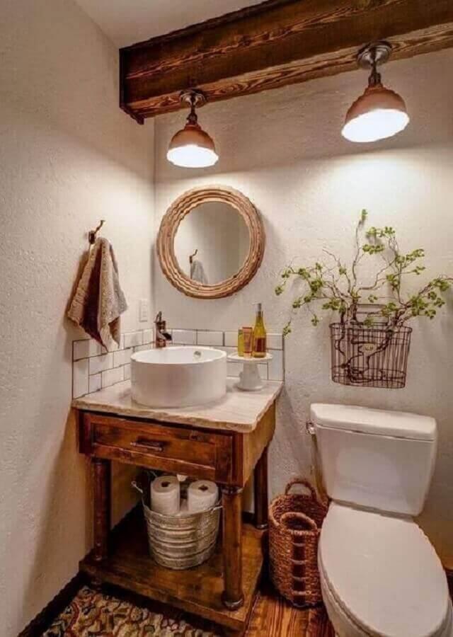 banheiro rústico decorado com espelho redondo e gabinete antigo Foto Jeito de Casa