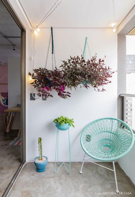 Cadeira acapulco azul com plantas suspensas