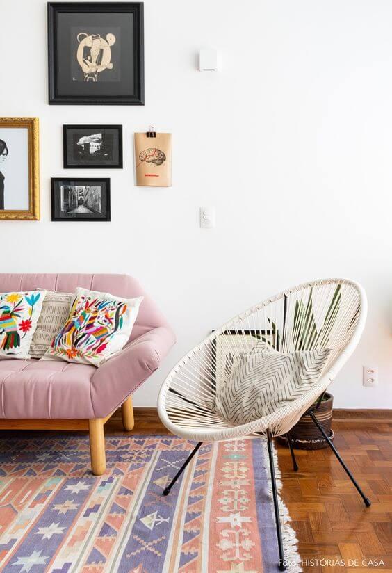 Cadeira acapulco branca na sala com sofá cor de rosa