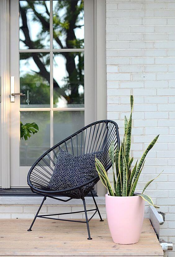 Cadeira preta acapulco com vaso de plantas