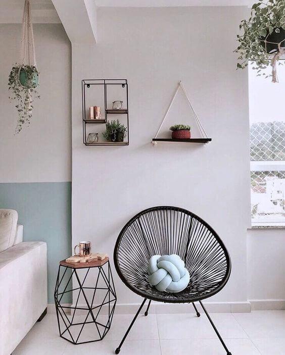 Cadeira acapulco preta com almofada de nó decorando a sala de estar moderna
