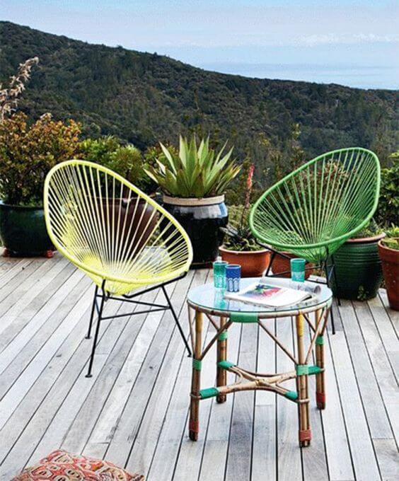 Cadeira acapulco amarela e verde na área externa de casa
