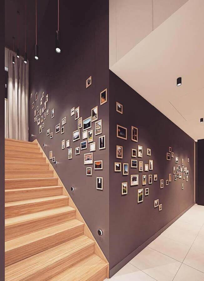 composição de quadros na parede cinza com escada de madeira Foto Behance