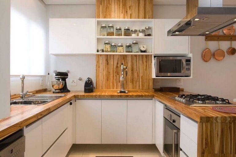 cozinha em U com bancada de madeira e armários planejados brancos Foto Webcomunica