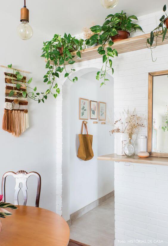 Prateleira da sala de jantar decorada com vaso de planta jiboia