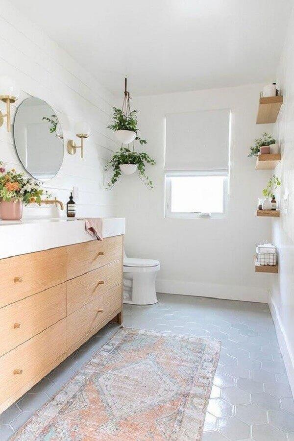 decoração com plantas no banheiro planejado com gabinete de madeira e espelho redondo Foto House Passion