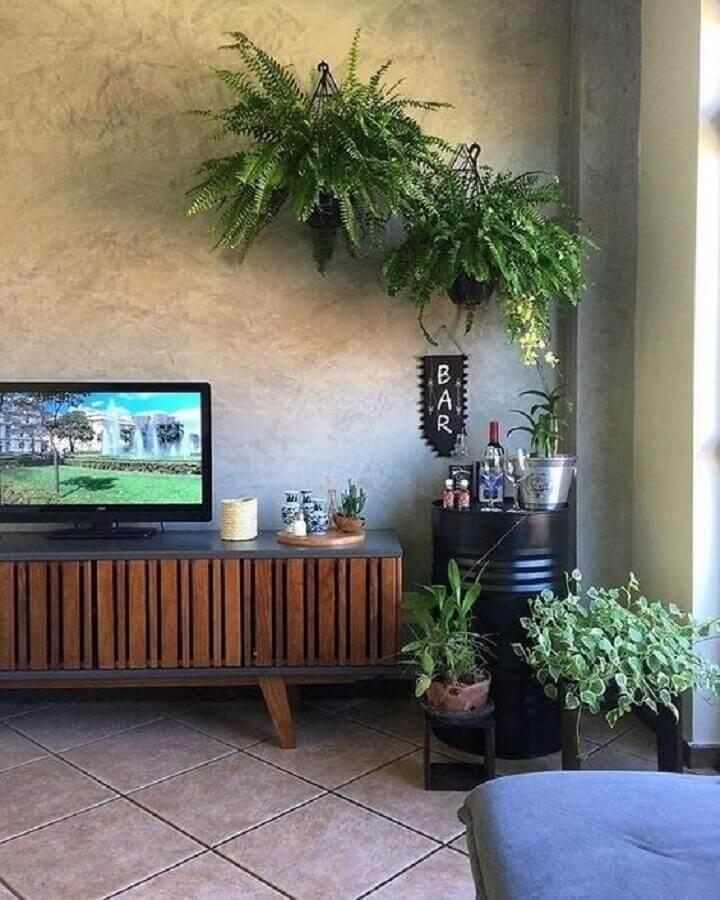 decoração com plantas pendentes para sala moderna com tonel preto para barzinho e rack de madeira Foto Ideias de Casa