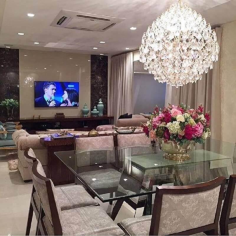 decoração sala de jantar com lustre de cristal e vaso de metal com arranjos de flores para mesa de jantar de vidro Foto Pinterest