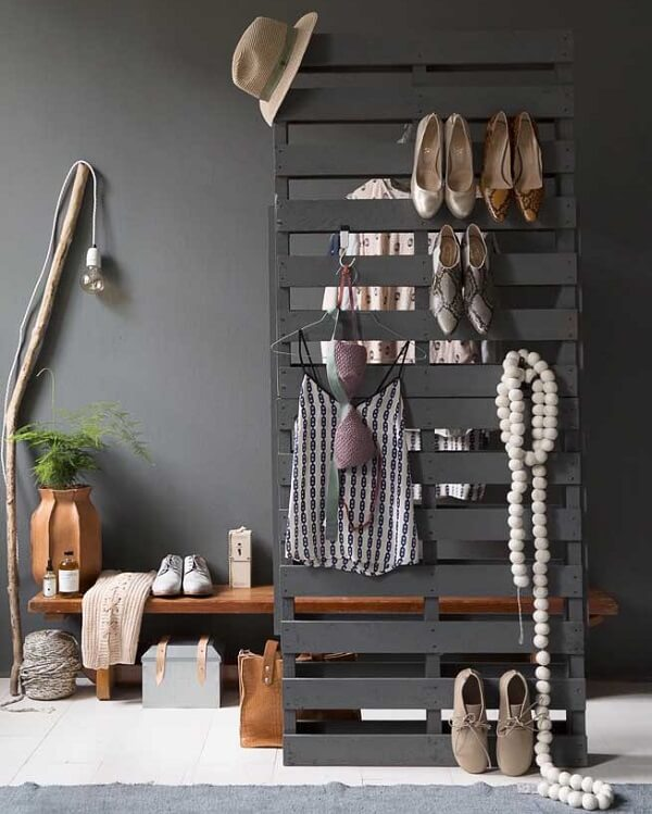 A estrutura do pallet pintada de cinza serve de suporte para roupas, sapatos e acessórios