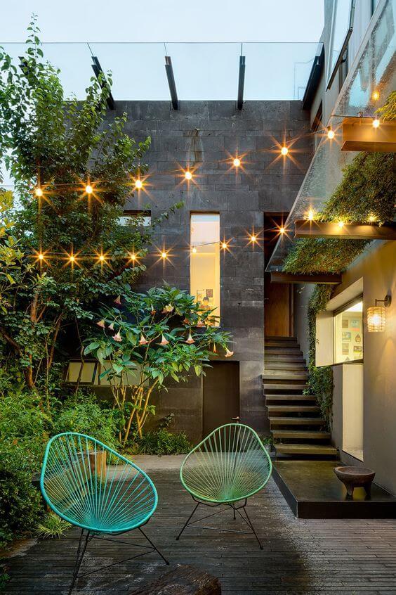 Cadeira acapulco verde e azul no jardim com luzes