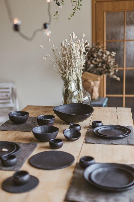 Jogo americano de tecido com travessas e pratos pretos