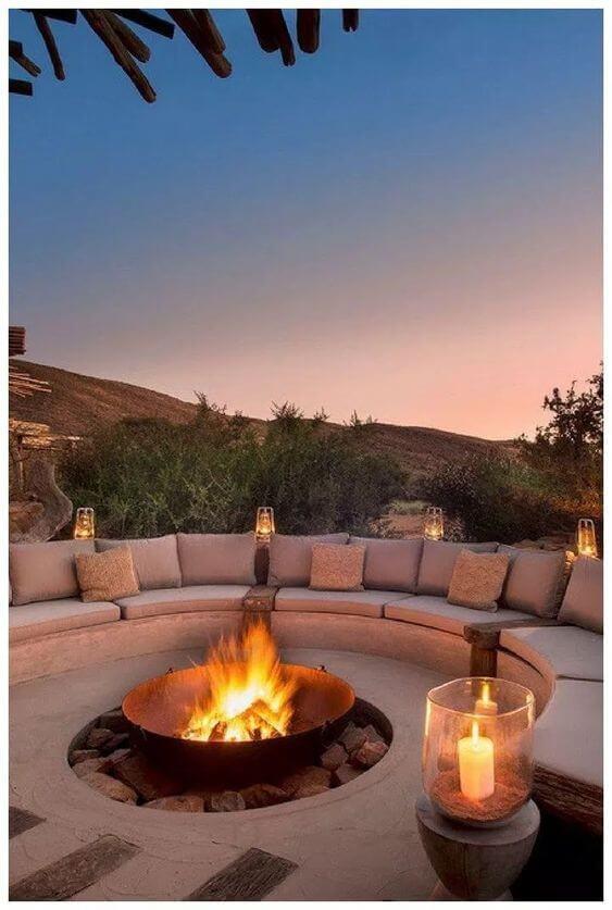 Lareira externa com sofá redondo no jardim