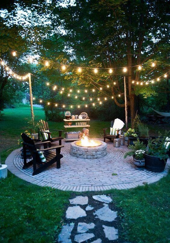 Lareira externa no jardim iluminado e poltronas de madeira