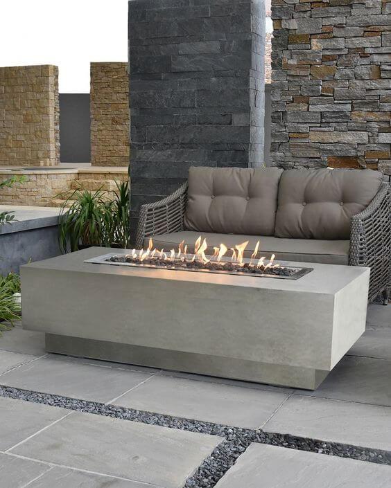 Jardim com lareira externa e sofá cinza moderno