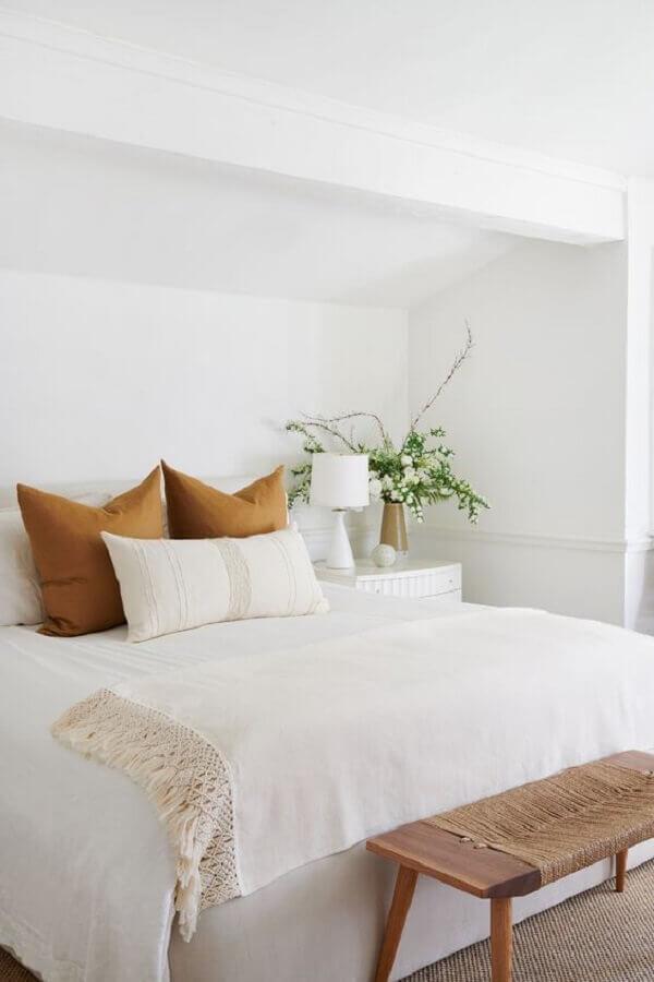 peseira para quarto de casal todo branco decorado com banco de madeira e almofada marrom Foto Pinterest