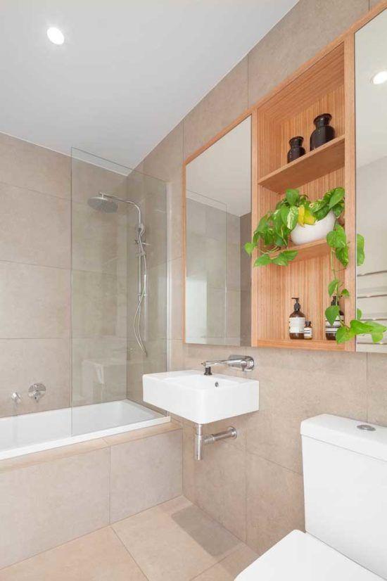 Banheiro moderno com vaso de planta jiboia nos armários