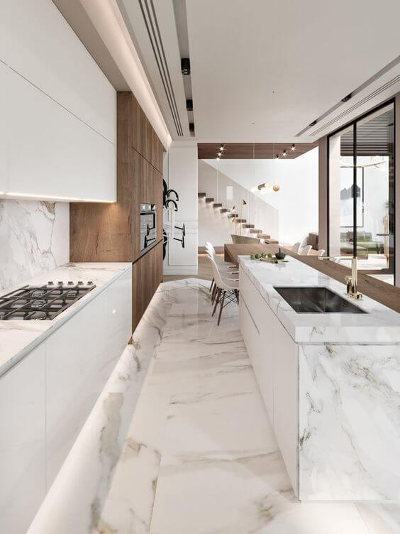 Cozinha com porcelanato marmorizado e armários brancos