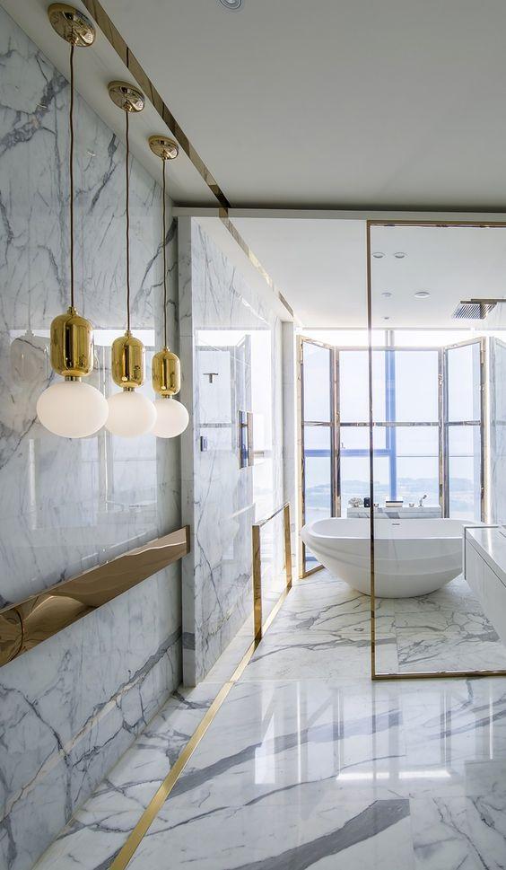 Porcelanato marmorizado no banheiro com detalhes dourados