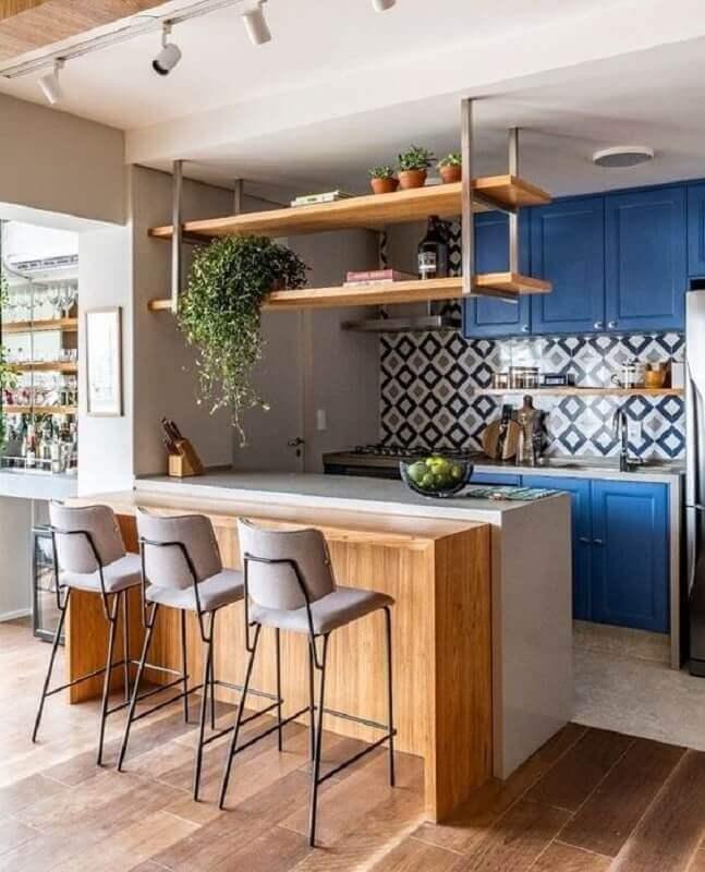 prateleira suspensa cozinha decorada com armários azuis e bancada de madeira Foto Arkpad