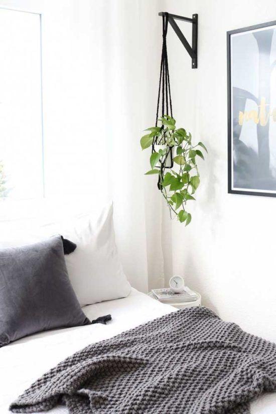 Quarto decorado com a planta jiboia acima do criado mudo