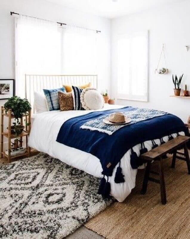 quarto de casal todo branco decorado com várias almofadas e peseira azul marinho com detalhes na barra Foto We Heart It
